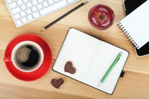 Coffee cup, cookies, red apple and office supplies